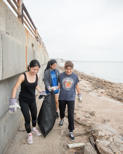 Nga Tran (left) Hannah Nguyen and  Ingrid Fernandez work together as they carry a bag of collected trash.