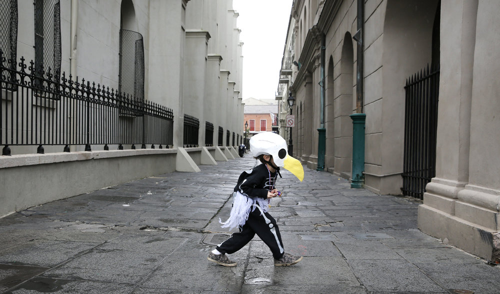 . Brody Bell, 6, of New Orleans, runs across Pierre Antoine Alley dressed as a bald eagle skeleton for Mardi Gras Day February 12, 2013 in New Orleans, Louisiana. He was parading with his parents who are members of a Skeleton krewe. Fat Tuesday, the traditional celebration on the day before Ash Wednesday and the begining of Lent, is marked in New Orleans with parades and marches through many neighborhoods in the city. (Photo by Rusty Costanza/Getty Images)