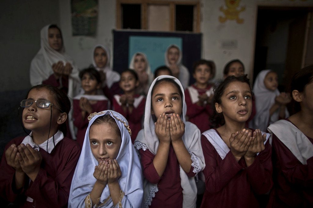 . Pakistani school children chant prayers during a special class to recognize the anniversary of Malala\'s shooting by Taliban, at a school in Rawalpindi, Pakistan, Wednesday, Oct. 9, 2013. One year after a Taliban bullet tried to silence Malala Yousufzai\'s demand for education, she has published a book and is a contender for the Nobel Peace Prize. But the militants threaten to kill her should she dare return home from Britain to Pakistan, and the principal at her old school says that as Malala\'s fame has grown, so has fear in her classrooms. (AP Photo/Muhammed Muheisen)