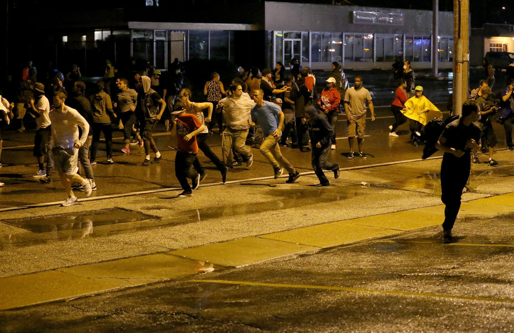 . People run as police start to fire tear gas at a crowd when they remained on the street after a midnight curfew on August 17, 2014 in Ferguson, Missouri. Police sprayed pepper spray, shot smoke, gas and flash grenades as violent outbreaks have taken place in Ferguson since the shooting death of Michael Brown by a Ferguson police officer on August 9th.  (Photo by Joe Raedle/Getty Images)