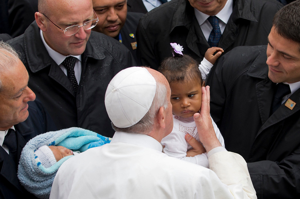 . Pope Francis kisses a baby girl as he is surrounded by security during his visit to the Varginha slum in Rio de Janeiro, Brazil, Thursday, July 25, 2013. Francis on Thursday visited one of Rio de Janeiro\'s shantytowns, or favelas, a place that saw such rough violence in the past that it\'s known by locals as the Gaza Strip.  (AP Photo/Victor R. Caivano)