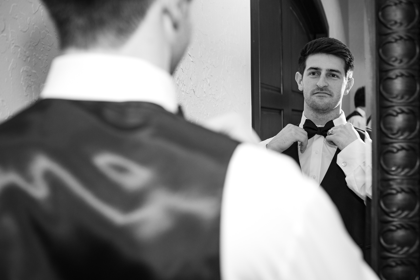 a groom tying his bowtie in the mirror before his wedding ceremony