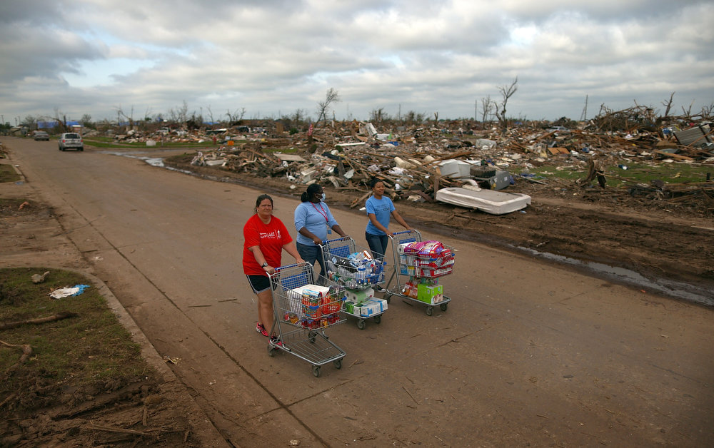 . (L-R) Volunteers Jaqi Castro, Angelica Morris-Smith and Cetoria Petties walk through a tornado ravaged neighborhood handing out supplies to residents and volunteers on May 27, 2013 in Moore, Oklahoma. Residents and volunteers observed the Memorial Day holiday by continuing to recover valuables from the destroyed neighborhoods one week after a massive tornado hit the area. The tornado of EF5 strength and two miles wide touched down May 20 killing at least 24 people and leaving behind extensive damage to homes and businesses. U.S. President Barack Obama promised federal aid to supplement state and local recovery efforts.  (Photo by Tom Pennington/Getty Images)