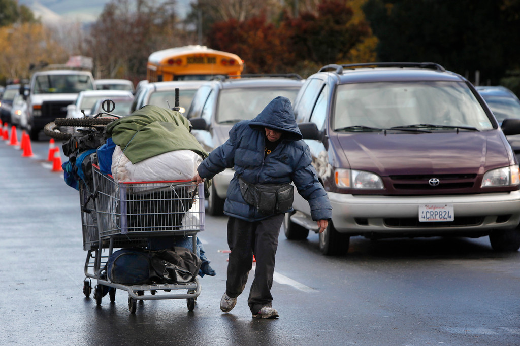""". Angie Hurst, 55, pulls what she calls a \""""double wheel\"""" full of her possessions down Story Road after leaving The Jungle homeless camp as it is closed Thursday, Dec. 4, 2014, in San Jose, Calif. (Karl Mondon/Bay Area News Group)"""