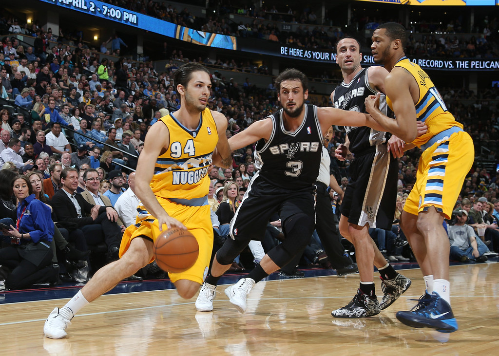 . From left to right, Denver Nuggets guard Evan Fournier, of France, works the ball inside as San Antonio Spurs guard Marco Belinelli, of Italy, covers while Spurs guard Manu Ginobili, of Argentina, and Nuggets forward Anthony Randolph look on in the first quarter of an NBA basketball game in Denver, Friday, March 28, 2014. (AP Photo/David Zalubowski)