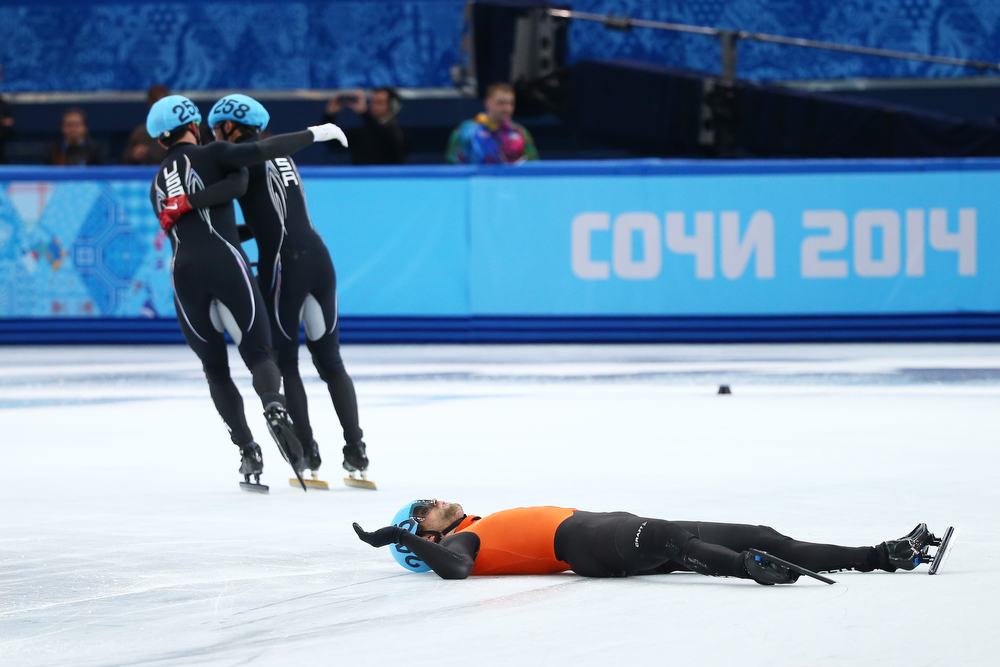 . Members of the United States shot track team celebrate winnig the silver medal while Daan Breeuwsma of teh Netherlands looks dejected after in the Short Track Men\'s 5000m Relay on day fourteen of the 2014 Sochi Winter Olympics at Iceberg Skating Palace on February 21, 2014 in Sochi, Russia.  (Photo by Ryan Pierse/Getty Images)
