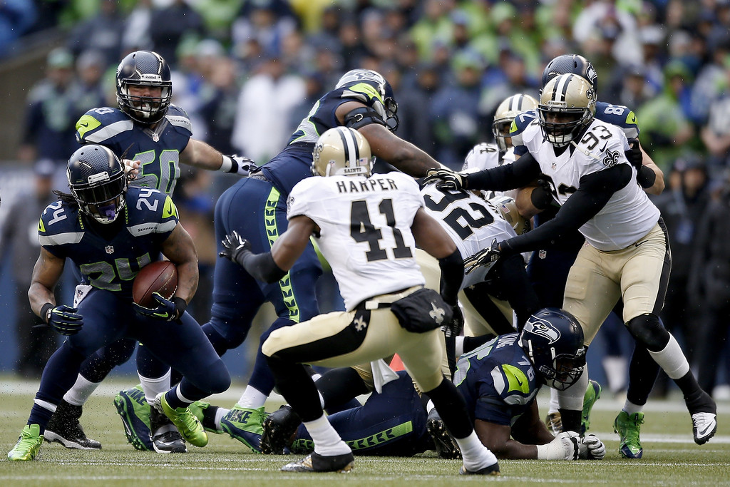. SEATTLE, WA - JANUARY 11:  Running back Marshawn Lynch #24 of the Seattle Seahawks runs the ball against strong safety Roman Harper #41 of the New Orleans Saints in the first half during the NFC Divisional Playoff Game at CenturyLink Field on January 11, 2014 in Seattle, Washington.  (Photo by Otto Greule Jr/Getty Images)
