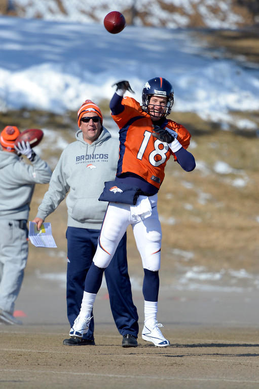 . Denver Broncos quarterbacks coach watches Denver Broncos quarterback Peyton Manning (18) pass during practice January 23, 2014 at Dove Valley.   (Photo by John Leyba/The Denver Post)