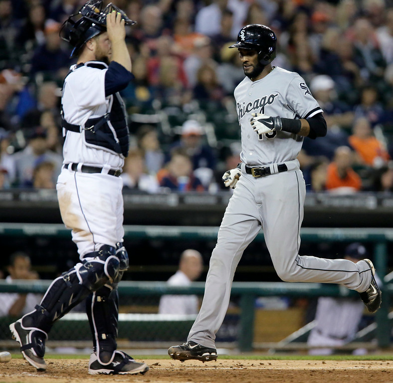 . Chicago White Sox\'s Alexei Ramirez scores past Detroit Tigers\' Bryan Holaday on a double by Chicago White Sox\'s Jose Abreu during the eighth inning of a baseball game Tuesday, July 29, 2014, in Detroit. The White Sox defeated the Tigers 11-4. (AP Photo/Duane Burleson)