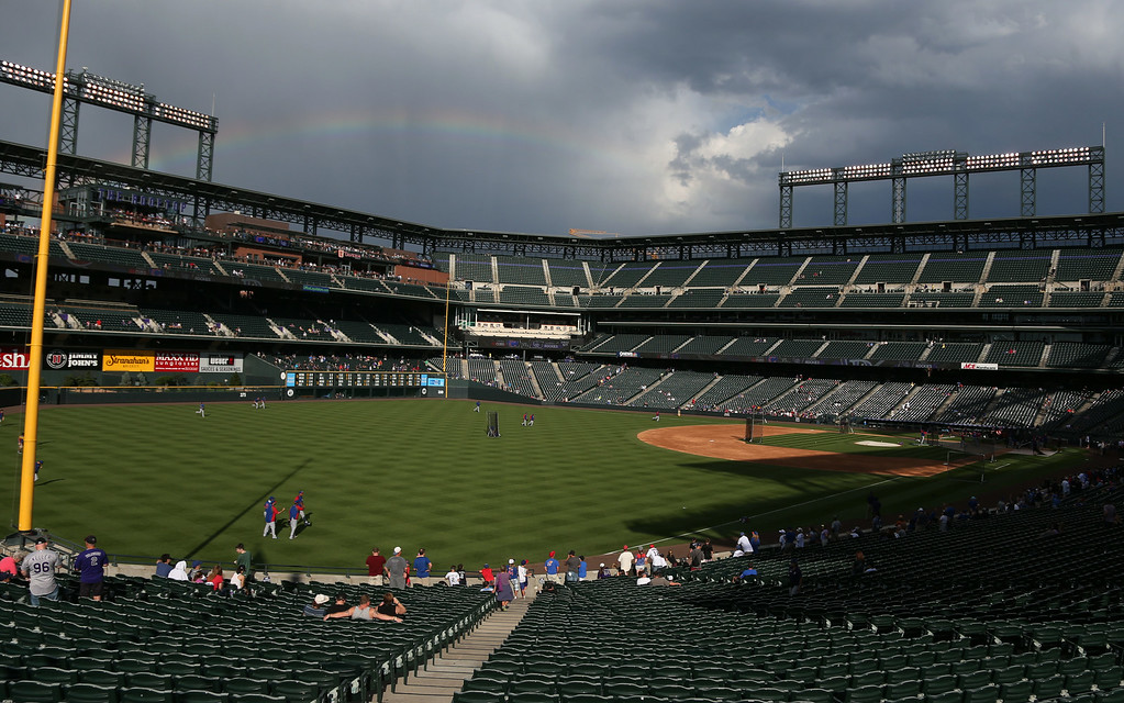 . A rainbow arcs over the right field stands of Coors Field in Denver as members of the Chicago Cubs warm up before facing the Colorado Rockies in a baseball game in Denver on Wednesday, Aug. 6, 2014. (AP Photo/David Zalubowski)