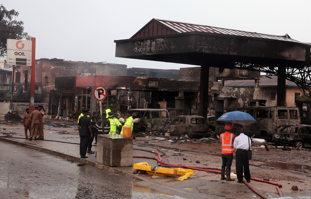 . Ghana security personnel stand near a gas station that exploded  in Accra, Ghana, Thursday, June 4, 2015. Flooding in Ghana\'s capital swept stored fuel into a nearby fire, setting off a huge explosion at a gas station that killed scores of people and set alight neighboring buildings, authorities said Thursday. (AP Photo/Christian Thompson)