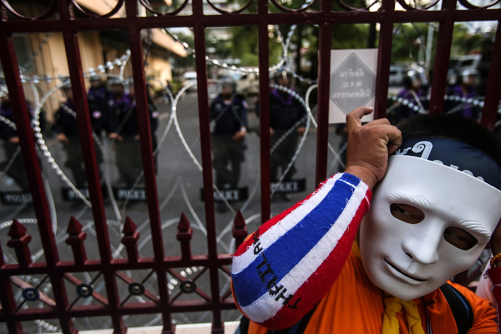 . An anti-government demonstrator wearing a mask stands in front of a gate as riot police officers keep watch during a protest at the police headquarters in Bangkok, Thailand, on Thursday, Nov. 28, 2013. Thai Prime Minister Yingluck Shinawatra, who survived a censure vote in parliament, called on protesters seeking her ouster to end their occupation of government buildings and come to the negotiating table for the good of the country. Photographer: Dario Pignatelli/Bloomberg
