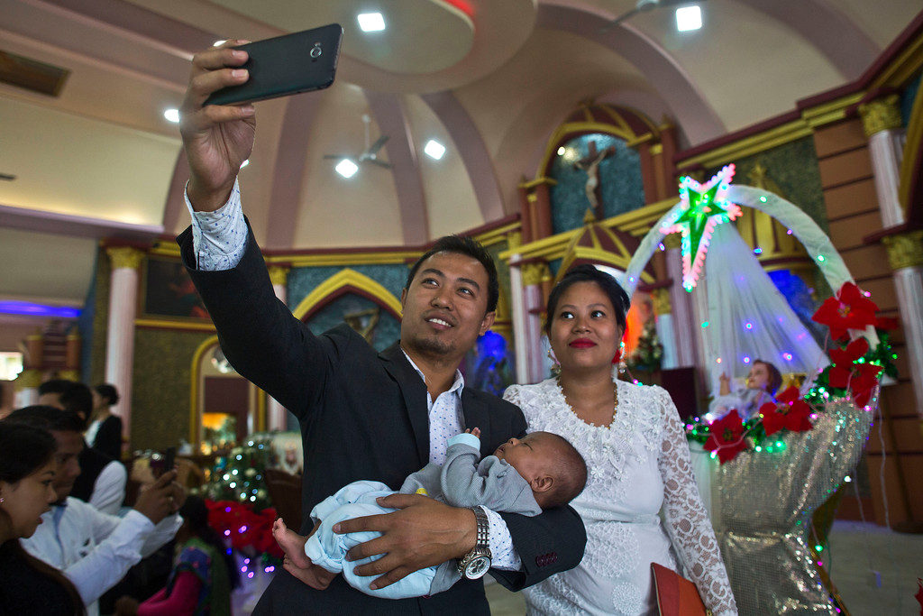 . An Indian Christian couple takes a selfie with their baby after offering prayers at a church in Gauhati, India, Monday, Dec. 25, 2017.  While Hindus and Muslims comprise the majority of the population in India, Christmas is a national holiday celebrated with much fanfare. (AP Photo/Anupam Nath)