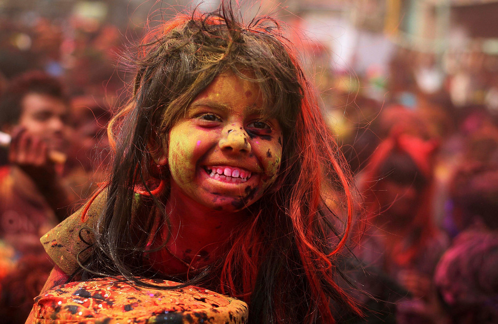 . An Indian girl, face smeared with colored powder, sits on the shoulder of her father during celebrations marking Holi, the Hindu festival of colors, in Gauhati, India, Monday, March 17, 2014. The festival also marks the advent of spring. (AP Photo/Anupam Nath)