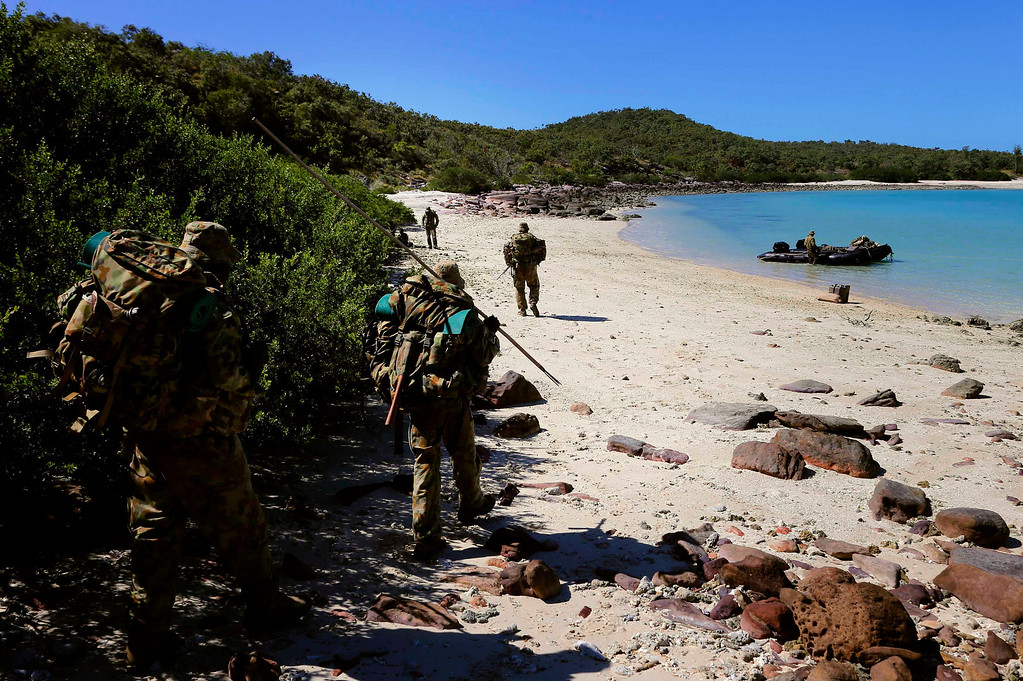 . Indigenous soldiers from Australia\'s North West Mobile Force (NORFORCE) unit carry their F88 Austeyr rifles as they walk along a beach on Wigram Island, part of the English Company Islands, located inside Arnhem Land in the Northern Territory, Australia July 19, 2013. NORFORCE is a surveillance unit that employs ancient Aboriginal skills to help in the seemingly impossible task of patrolling the country\'s vast northwest coast. NORFORCE\'s area of operations is about 1.8 million square km (700,000 square miles), covering the Northern Territory and the north of Western Australia. Aboriginal reservists make up a large proportion of the 600-strong unit, and bring to bear their knowledge of the land and the food it can provide. Fish, shellfish, turtle eggs and even insects supplement rations during the patrol, which is on the lookout for illegal foreign fishing vessels and drug smugglers, as well as people smugglers from neighboring Indonesia.  Picture taken July 19, 2013. REUTERS/David Gray
