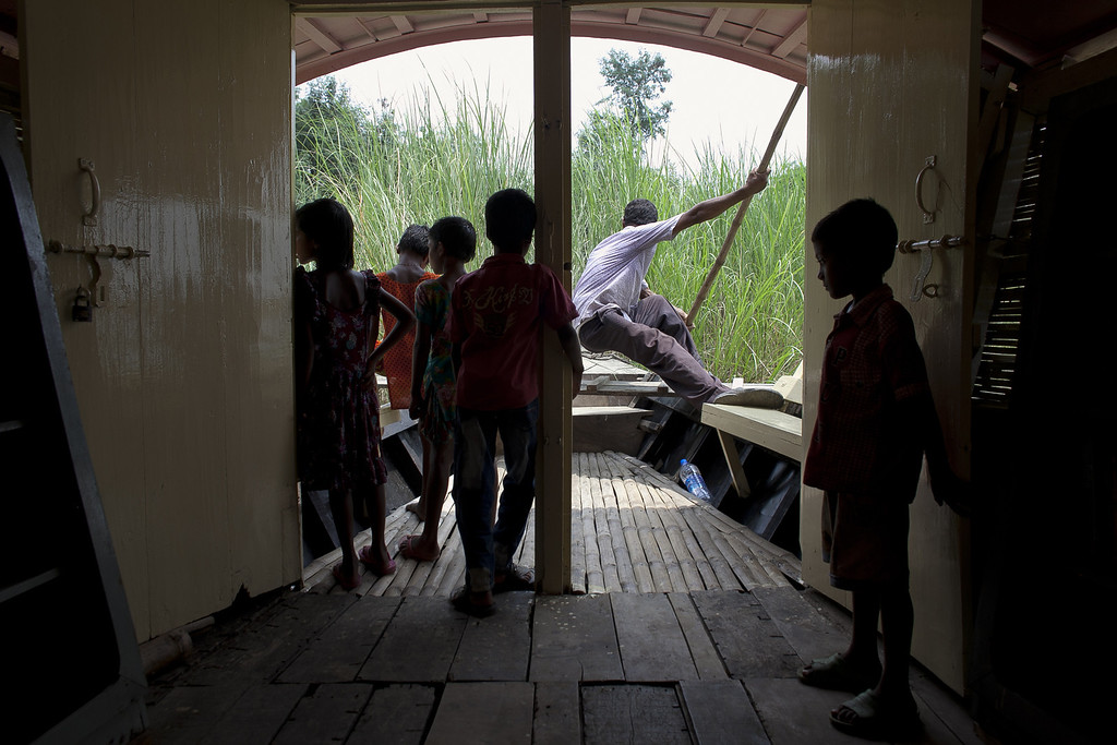 """. A boatman steers the school towards land as children are let out from class for the day from a solar powered \""""floating school\"""" operated by Shidhulai Swanirvar Sangstha May 20, 2014 in Pabna district, Bangladesh. (Photo by Allison Joyce/Getty Images)"""