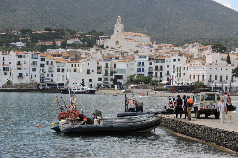 Whitewashed buildings crowd the Cadaques harbour in Spain.