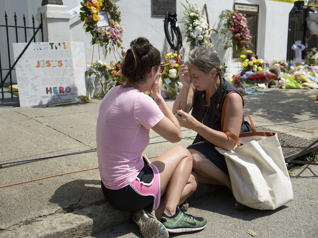 . Maranda Mincey  (L) and Stewart Watson sit together at a makeshift memorial outside the Emanuel AME Church June 19, 2015 in Charleston, South Carolina. The young white man suspected of gunning down nine people at a black church in South Carolina has been charged with their murders, police said Friday, as the state\'s governor called for him to face the death penalty.The carnage at the Emanuel African Methodist Episcopal Church in Charleston was the worst attack on a US place of worship in decades, and comes at a time of revived racial tensions in many parts of the country.AFP PHOTO/BRENDAN  SMIALOWSKI/AFP/Getty Images