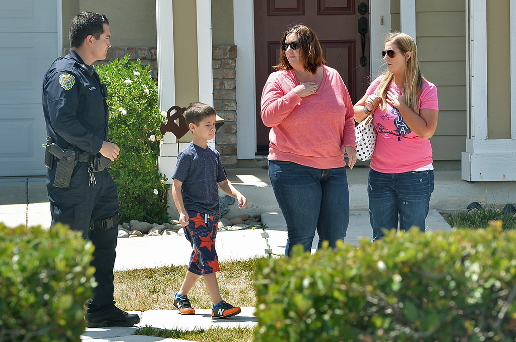 . A Brentwood police officer, left, talks to visitors to the home of  Sgt. Scott Lunger of the Hayward Police Department, who was shot and killed early Wednesday morning after making a traffic stop on a driver who was driving erratically in Hayward, as friends or family arrive at the home in Brentwood, Calif., on Wednesday, July 22, 2015. (Dan Rosenstrauch/Bay Area News Group)