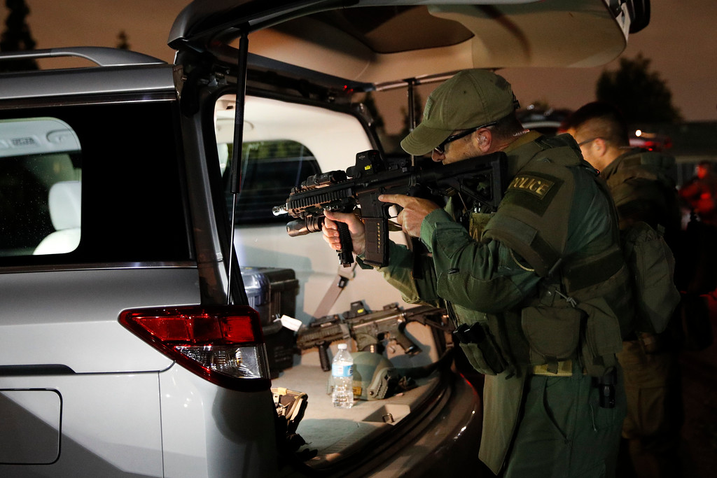 . An ATF agent checks his weapon as he gets ready for a raid Wednesday morning, May 17, 2017, in Los Angeles. Hundreds of federal and local law enforcement fanned out across Los Angeles, serving arrest and search warrants as part of a three-year investigation into the violent and brutal street gang MS-13. (AP Photo/Jae C. Hong)