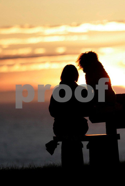 Woman sitting with her dog on a picnic table at Ecola State Park, Oregon, watching the sun set.