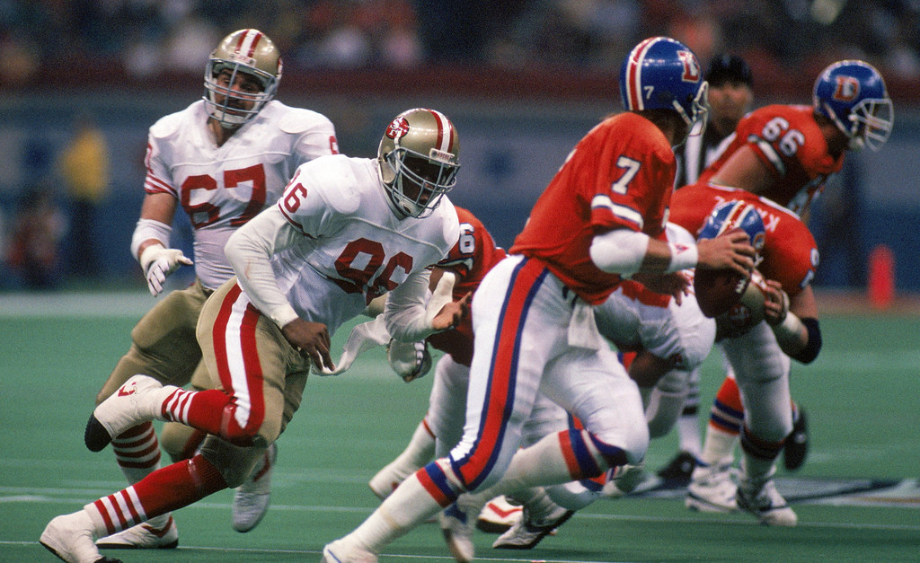 . Defensive end Daniel Stubbs #96 of the San Francisco 49ers pursues Denver Broncos quarterback John Elway #7 in Super Bowl XXIV at Louisiana Superdome on January 28, 1990 in New Orleans, Louisiana.  The 49ers won 55-10.  (Photo by George Rose/Getty Images)