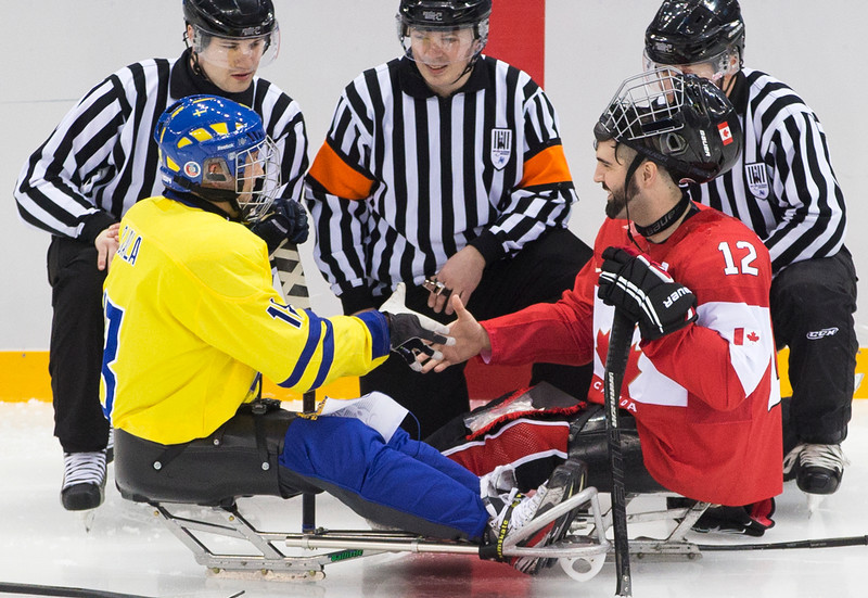 . Greg Westlake of Canada, right, and Peter Ojala of Sweden, left, shake hands before the ice sledge hockey match at the Shayba Arena at the 2014 Winter Paralympics in Sochi, Russia, Saturday, March 8, 2014.  Canada went on to win the match 10-1. (AP Photo/Pavel Golovkin)
