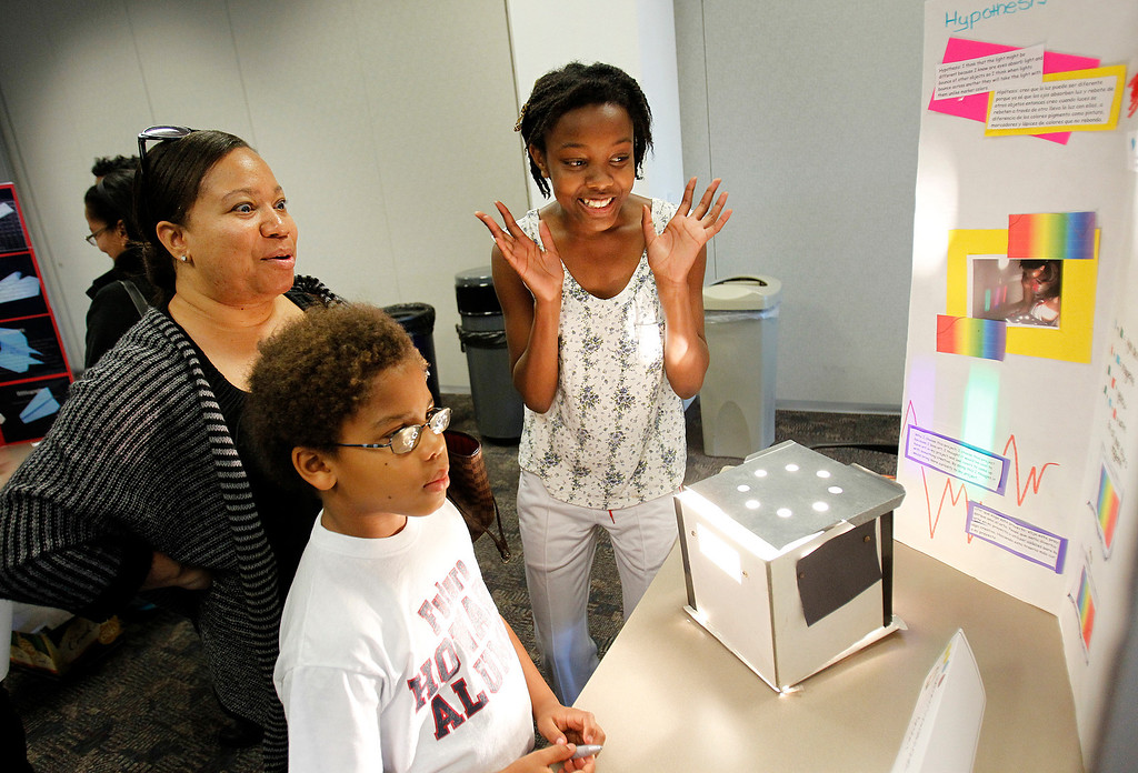 . At right, Natania JonesMitchell, a 7th grader from Keys Middle School explains her project, which compares mixing colored light with mixing marker colors, to Melanie Adams, left,  and her son Bradley Adams, 8, center, at the eleventh annual Dr. Frank S. Greene Scholars Program Science Fair, at Cypress Semiconductor headquarters, in San Jose, Calif. on Saturday, January 26, 2013.   (LiPo Ching/Staff)