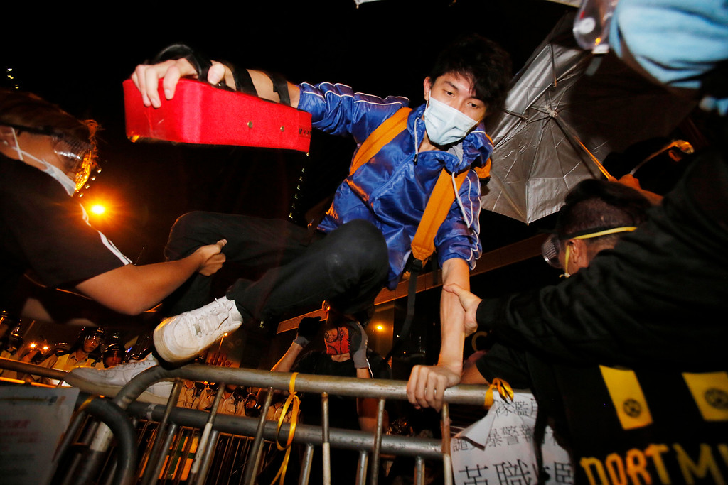 . A pro-democracy protester jumps a barricade as riot police move into their encampment in the Mong Kok district of Hong Kong, Saturday, Oct. 18, 2014. Hong Kong riot police battled with thousands of pro-democracy protesters for control of the city\'s streets Saturday, using pepper spray and batons to hold back defiant activists who returned to a protest zone that officers had partially cleared. (AP Photo/Wally Santana)