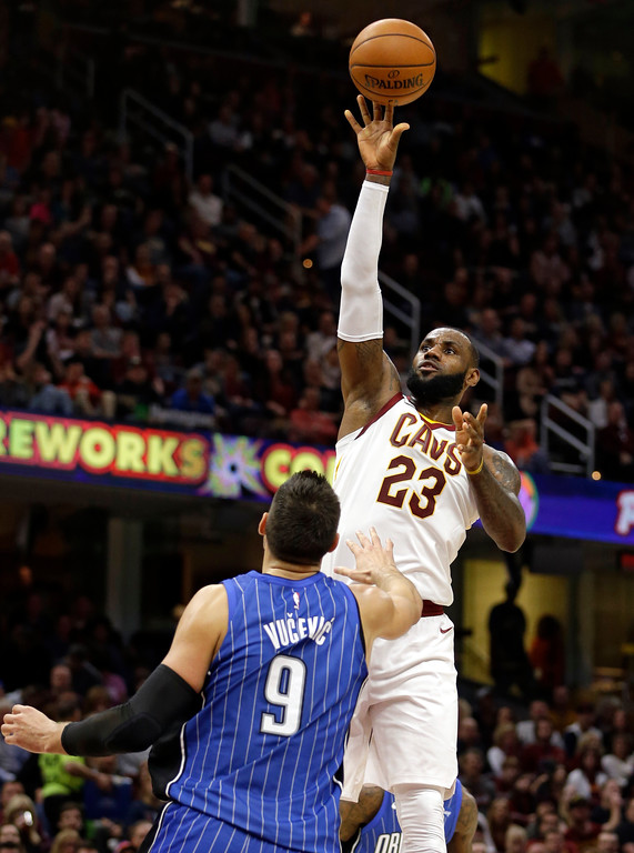 . Cleveland Cavaliers\' LeBron James (23) shoots over Orlando Magic\'s Nikola Vucevic (9), from Montenegro, in the first half of an NBA basketball game, Saturday, Oct. 21, 2017, in Cleveland. (AP Photo/Tony Dejak)