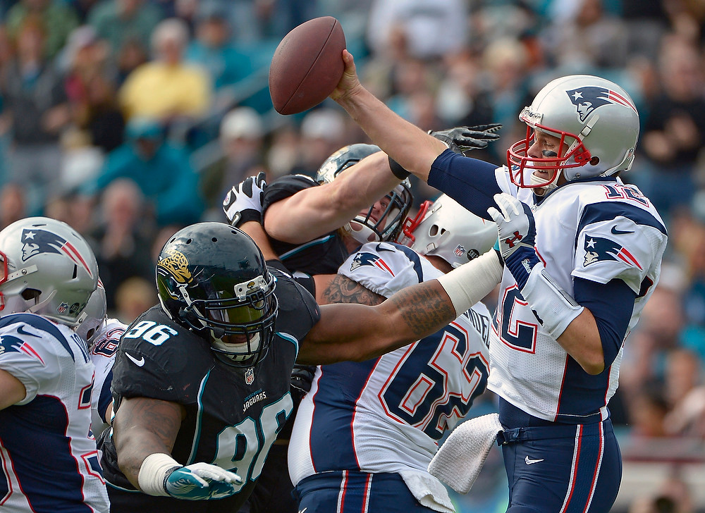 . New England Patriots quarterback Tom Brady, right, makes a move to get away from Jacksonville Jaguars defensive tackle Terrance Knighton (96) during the first half of an NFL football game on Sunday, Dec.  23, 2012, in Jacksonville, Fla. The Patriots won the game 23-16. (AP Photo/Phelan M. Ebenhack)
