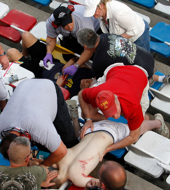 . Injured spectators are treated after a crash at the conclusion of the NASCAR Nationwide Series auto race Saturday, Feb. 23, 2013, at Daytona International Speedway in Daytona Beach, Fla. Driver Kyle Larson\'s car hit the safety fence sending car parts and other debris flying into the stands. (AP Photo/David Graham)