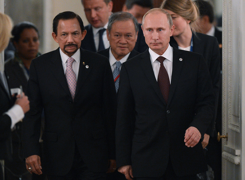 . In this handout image provided by Host Photo Agency, Russian Vladimir Putin (R) and the Sultan of Brunei Hassanal Bolkiah (L) arrive at a working dinner for G20 Summit members September 5, 2013 in St. Petersburg, Russia.  (Photo by Ramil Sitdikov/Host Photo Agency via Getty Images)