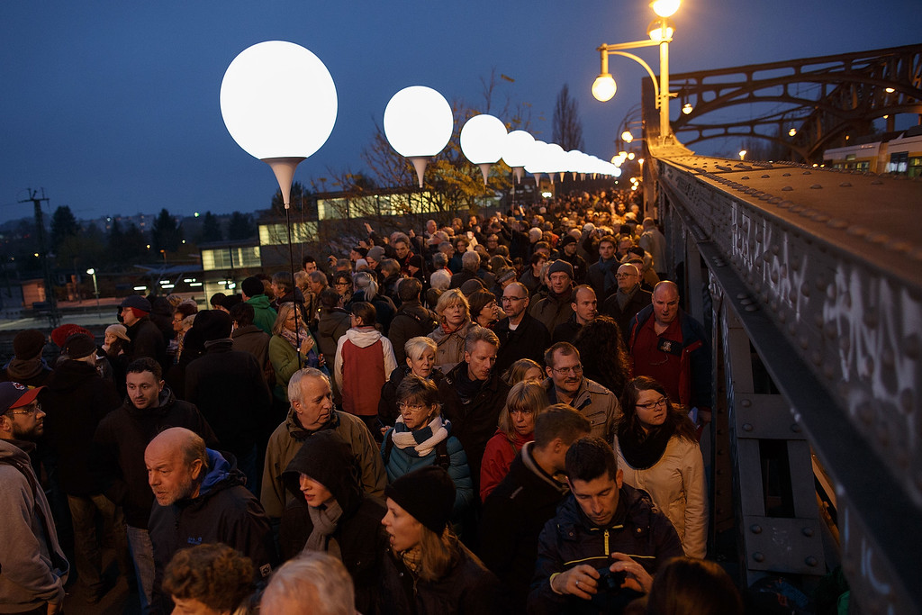 . BERLIN, GERMANY - NOVEMBER 09:  People gather to look the illumination on Boesebruecke bridge in Bornholmer Strasse, where 25 years before thousands of East Germans first crossed unimpeded though a gate of the Berlin Wall into West Berlin, on the 25th anniversary of the fall of the Wall on November 9, 2014 in Berlin, Germany. The city of Berlin is commemorating the 25th anniversary of the fall of the Berlin Wall with an installation of 6,800 lamps coupled with illuminated balloons along a 15km route where the Wall once ran and divided the city into capitalist West and communist East. The fall of the Wall on November 9, 1989, was among the most powerful symbols of the revolutions that swept through the communist countries of Eastern Europe and heralded the end of the Cold War. Built by the communist authorities of East Germany in 1961, the Wall prevented East Germans from fleeing west and was equipped with guard towers and deadly traps.  (Photo by Carsten Koall/Getty Images)