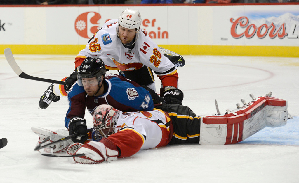 . DENVER, CO. - FEBRUARY 28: Dennis Wideman (26) of the Calgary Flames and David Jones (54) of the Colorado Avalanche land on top of G Joey MacDonald (35) of the Calgary Flames after making a save in the third period February 28, 2013 at Pepsi Center. The Colorado Avalanche defeated the Calgary Flames 5-4. (Photo By John Leyba/The Denver Post)