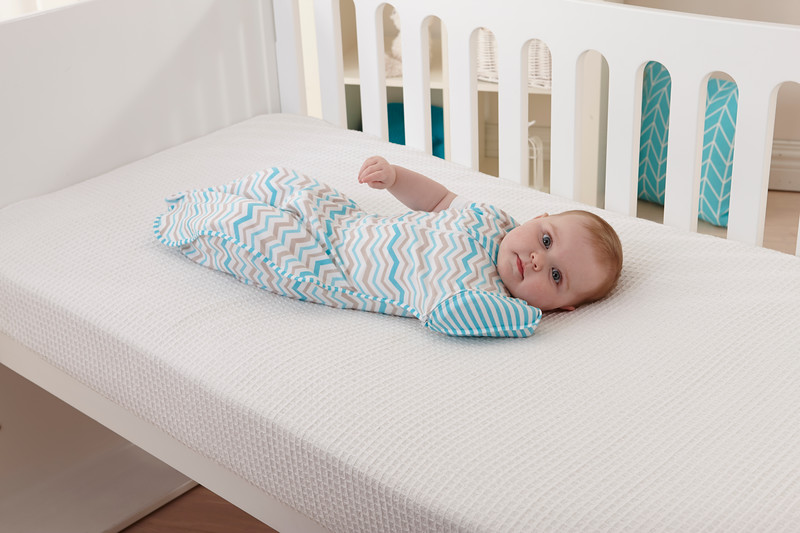 Love_To_Dream_Stage_2_5050_Zigzag_Turquoise_Lifestyle_Side_View_In_Cot_Arm_Down.jpg