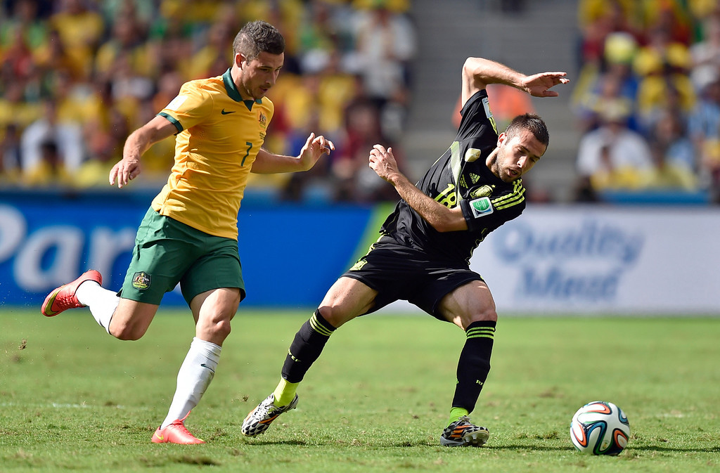 . Spain\'s Jordi Alba, right, and Australia\'s Mathew Leckie challenge for the ball during the group B World Cup soccer match between Australia and Spain at the Arena da Baixada in Curitiba, Brazil, Monday, June 23, 2014. (AP Photo/Martin Meissner)