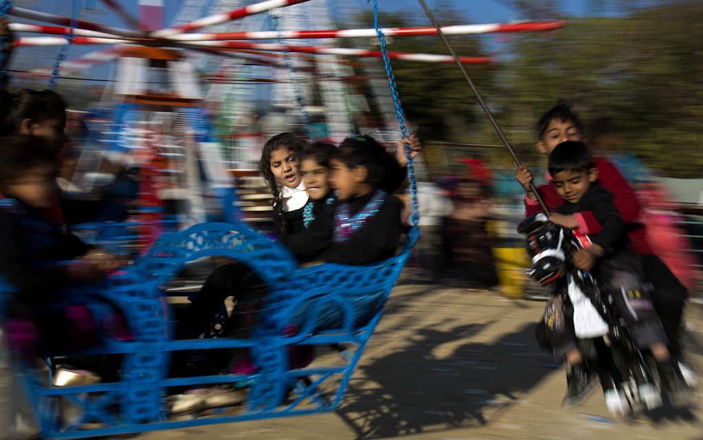 . Pakistani Christian children celebrate Christmas on a ride in Islamabad\'s slums, Pakistan. Wednesday, Dec. 25, 2013. Christians are a minority in Pakistan and constitute about 1.6% of the country\'s population. (AP Photo/B.K. Bangash)