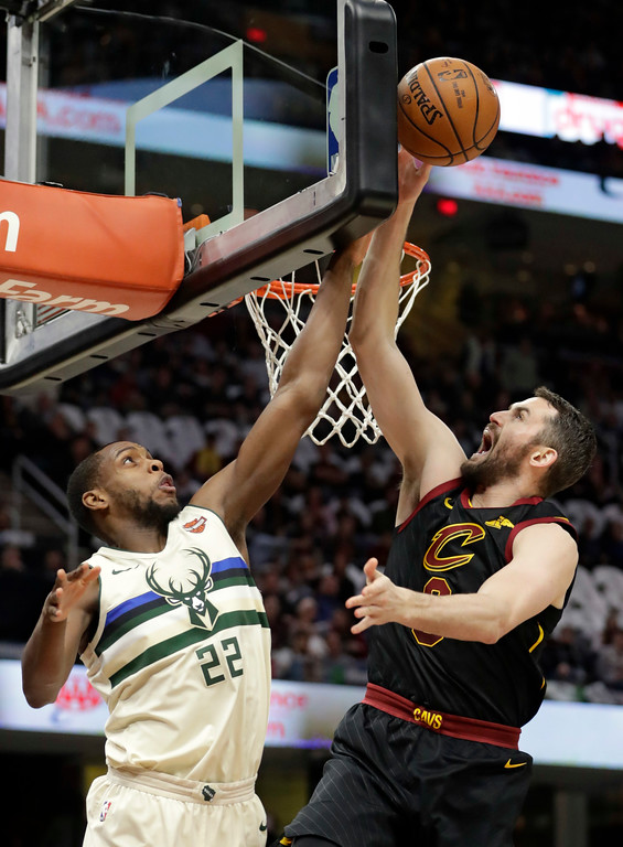 . Milwaukee Bucks\' Khris Middleton (22) blocks a shot by Cleveland Cavaliers\' Kevin Love (0) in the first half of an NBA basketball game, Monday, March 19, 2018, in Cleveland. (AP Photo/Tony Dejak)