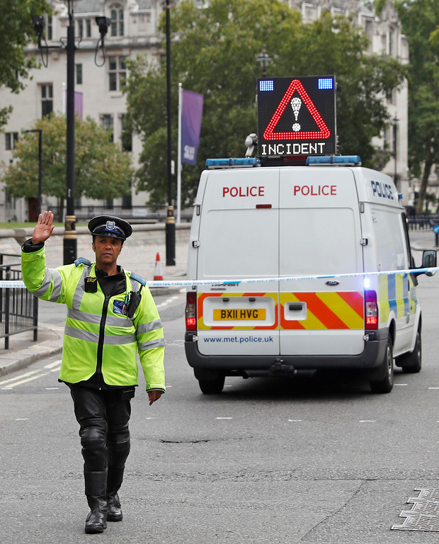 . A police officer gestures as he stands in a road in central London, after a car crashed into security barriers outside the Houses of Parliament, in London, Tuesday, Aug. 14, 2018. London police say that a car has crashed into barriers outside the Houses of Parliament and that there are a number of injured. (AP Photo/Alastair Grant)
