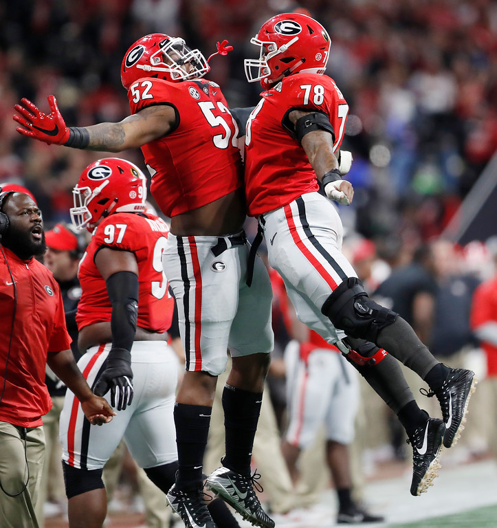 . Georgia\'s Trenton Thompson and Tyler Clark (52) celebrate after forcing Alabama to punt during the first half of the NCAA college football playoff championship game Monday, Jan. 8, 2018, in Atlanta. (AP Photo/David Goldman)