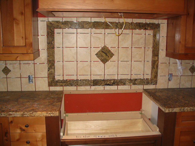 The backsplash tile is installed, though not grouted, behind the cooktop.