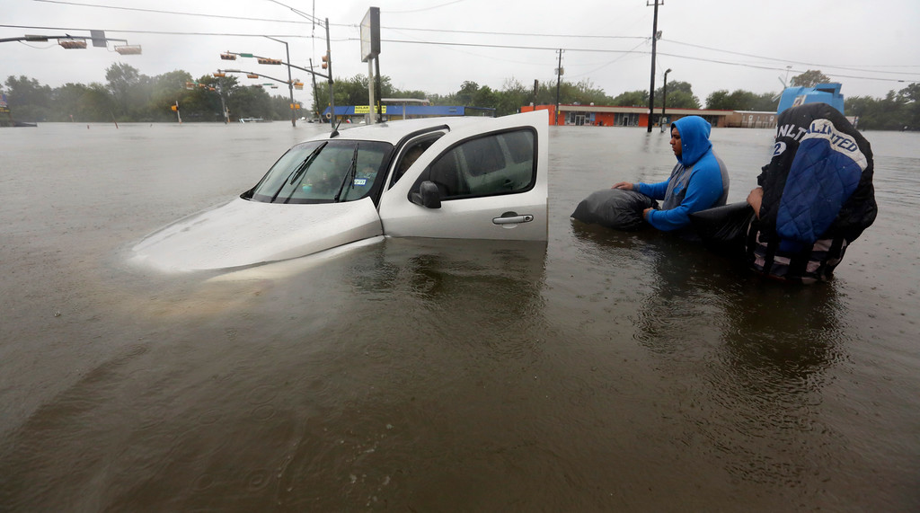 . Conception Casa, right, and his friend Jose Martinez, center, check on Rhonda Worthington after her car become stuck in rising floodwaters from Tropical Storm Harvey in Houston, Texas, Monday, Aug. 28, 2017. The two men were evacuating their home that had become flooded when they encountered Worthington\'s car floating off the road. (AP Photo/LM Otero)