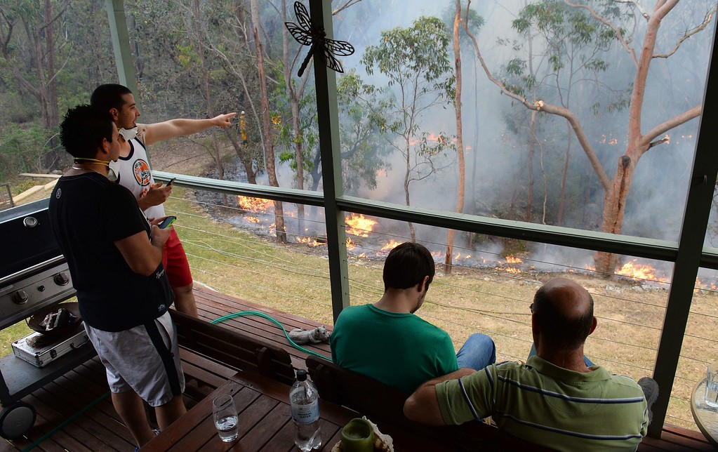 . Local residents watch the containment fires from the balcony on his house at Faulconbridge in the Blue Mountains on October 22, 2013. Firefighters on October 22 deliberately merged two major blazes in southeastern Australia in a desperate battle to manage the advancing infernos as weather conditions worsen. AFP PHOTO/William  WEST/AFP/Getty Images