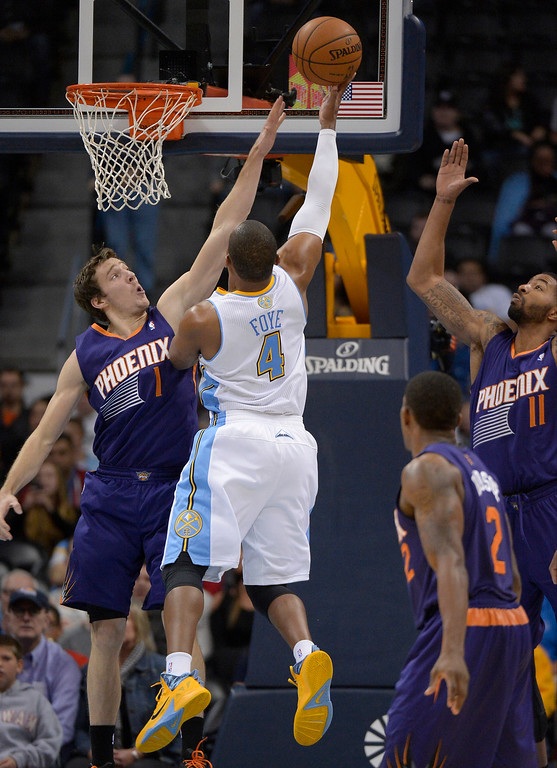 . Denver Nuggets point guard Randy Foye (4) takes a shot over Phoenix Suns point guard Goran Dragic (1) during the third quarter October 23, 2013 at Pepsi Center. (Photo By John Leyba/The Denver Post)