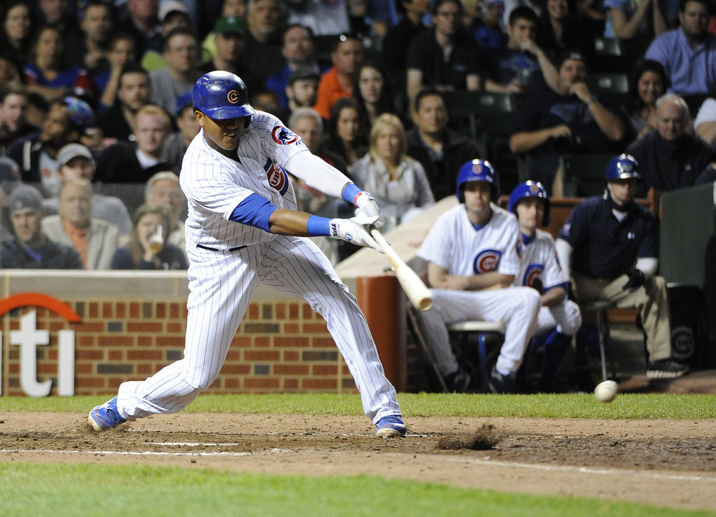 . Starlin Castro #13 of the Chicago Cubs hits an RBI single during the seventh inning against the Colorado Rockies on May 15, 2013 at Wrigley Field in Chicago, Illinois.   (Photo by David Banks/Getty Images)