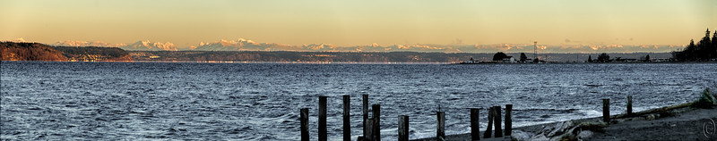 05 Jan 17As promised , here is a shot of something I've never before seen. You are looking across a part of Puget Sound with almost, not quite, the entire range of the Cascade Mountains in view at one time. The shot is somewhat deceiving in that you are viewing roughly a 135 mile span of rock. Mt Baker is at the left had edge of the frame and Mt Rainier is out of view about an inch beyond the right hand edge and not included in the photo(s). This is a 7 frame pano. I've shared many shots from this location, but this was a first for me, to see the entire range all clearly visible, with snow no-less, at one time. For those of you who are unfamiliar with our weather this may not seem like much, but for me it was a tremendous treat so I thought I should share. The thin light line at sea level across most of the image is a mirage are frequent occurrence when looking across the sound as we are in this image. For a better idea of what is happening, watch this video. I saw this same type of activity from McMurdo Station in Antarctica.  Seven frames merged into a single composite with several adjustments made to get everything balanced.  Nikon D300s; 18 - 200; Aperture Priority;  ISO 200; 1/250 sec @ f / 5.6.