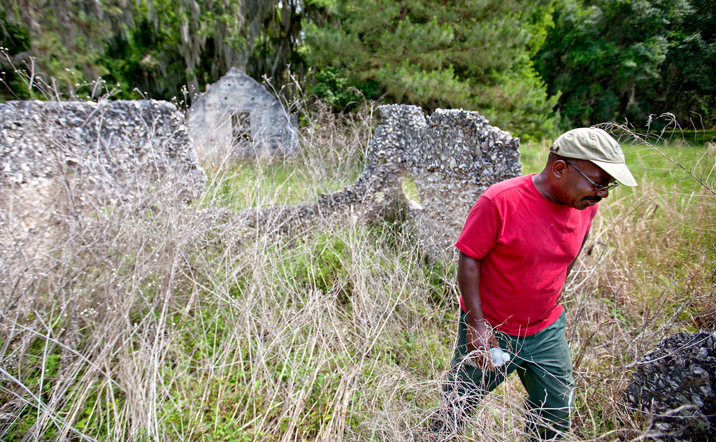 . Ire Gene Grovner walks through remnants of the old slave\'s quarters at the Chocolate Plantation where his ancestors lived some eight generations ago on Sapelo Island, Ga. on Thursday, May 16, 2013 photo. Grovner is one of roughly 47 residents, most of them descendants of West African slaves known as Geechee, who remain on Sapelo Island, the coastal Georgia island where their ancestors were brought to work a plantation in the early 1800s. (AP Photo/David Goldman)