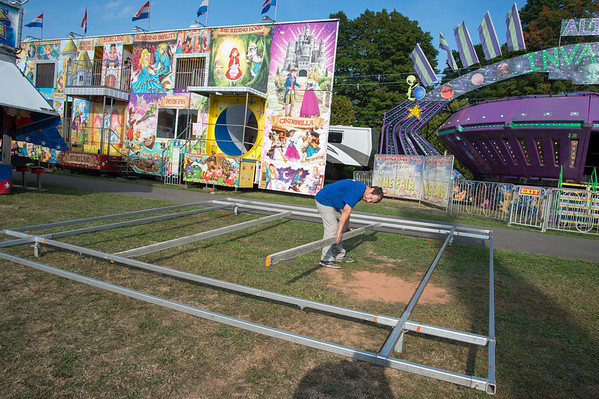 09/11/19 Wesley Bunnell | StaffrrCarnival workers assemble attractions ahead of the Berlin Fair taking place this weekend. Aaron Krever assembles the base for one of the carnival games.