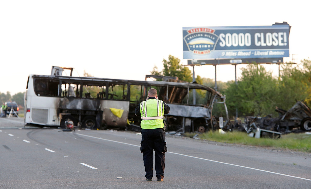 . A California Highway Patrol Officer photographs the crash scene, Friday, April 11, 2014, where a tour bus and a FedEX truck crashed on Interstate 5 Thursday in Orland, Calif.  At least ten people were killed and dozens injured in the fiery crash between the truck and a bus carrying high school students on a visit to a Northern California College. (AP Photo/Rich Pedroncelli)